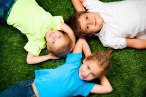 small kids lie on the green grass